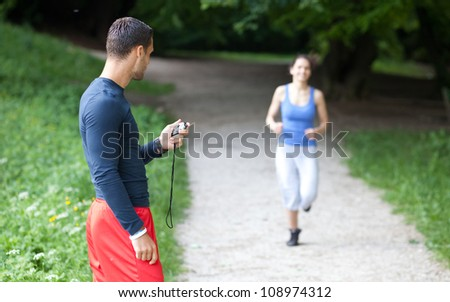 Personal trainer timing a female runner. Selective focus. - stock photo