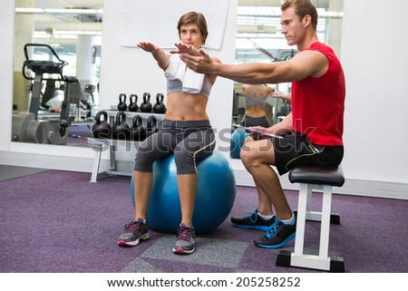 Personal trainer with client sitting straight on exercise ball at the gym