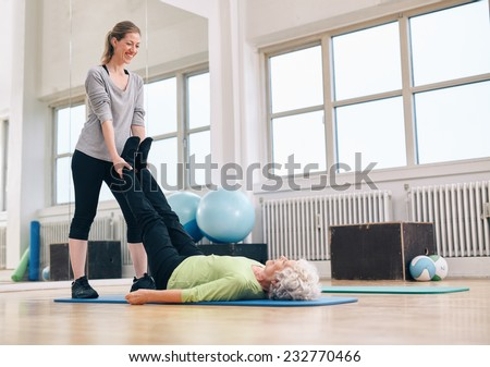 Personal trainer working with client on exercise mat at the gym. Instructor holding legs of senior woman exercising.