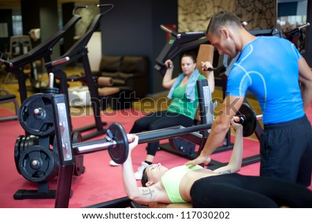 Personal trainer working with his client on bench press exercise. At the gym. Selective focus.