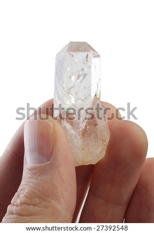 persons fingers holding a  large clear quartz crystal on white - stock photo