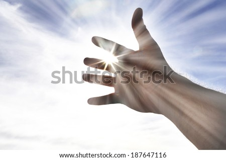Persons hand reaching in hope towards heaven with sunlight shining through - stock photo
