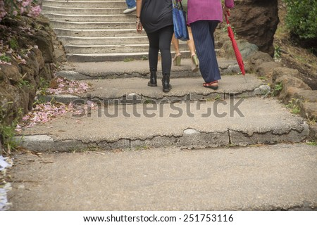persons legs in stairs, summer spring Girl help support grandmother going up to stairs Senior woman based on red umbrella between stone mountains with spring flower lie on way - stock photo