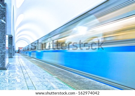 Perspective and diminishing wide angle view of modern light blue illuminated and spacious public metro marble abstract station, fast blurred trail of quick urban train in vanishing traffic motion way - stock photo