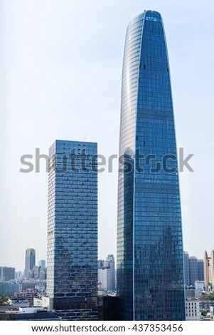 Perspective and underside angle view to textured background of modern glass building skyscrapers over blue cloudy sky - stock photo