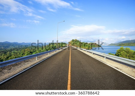 Perspective Black asphalt road with the Line Canal and the side rail steel stretching endlessly in a straight line to the forest under blue sky. - stock photo
