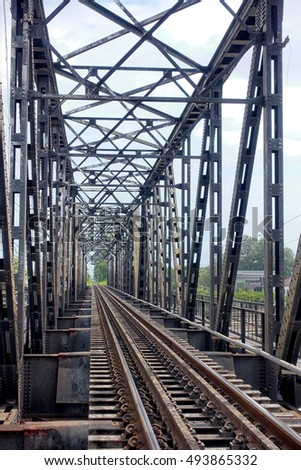 perspective of a rusty train bridge crossing the river in Ratchaburi, Thailand.