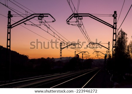 Perspective of the catenary and the railroad tracks, backlit, at dusk, with a purple sky - stock photo