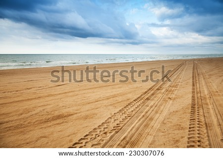 Perspective of tyre tracks on sandy beach with dark blue cloudy sky - stock photo