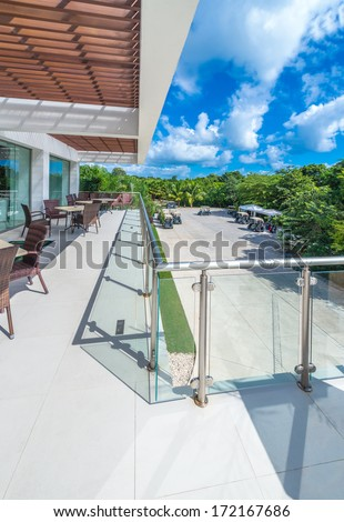 Perspective, outlook at the modern stylish balcony, deck, patio of the restaurant, cafe, bar with glass and steel railing. Luxury Mexican resort. Exterior, interior design.
