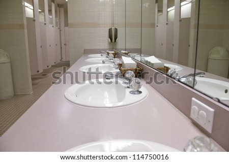 Perspective shot of a counter-top with five sinks and mirrors - stock photo