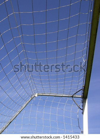 Perspective shot of soccer net against clear blue sky