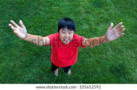 Perspective view of a smiling boy reaching to the sky - stock photo