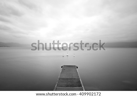 Perspective view of a steel pier in a completely calm lake with sky, clouds and mountains in background. Long exposure and white and black image. - stock photo