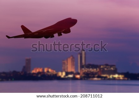 perspective view of jet airliner in flight with city background , use for air transport ,journey and travel industry business - stock photo