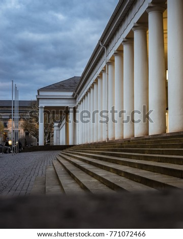 Perspective view of old stairs and an ancient greek style building with a series of white big columns in a cloudy day at twilight.