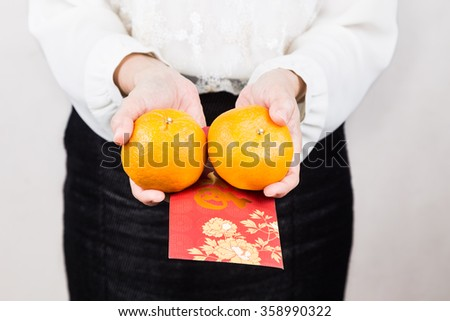 Perspective view of woman giving mandarin oranges and red envelop with Good Luck character, a tradition during Chinese New Year celebration - stock photo