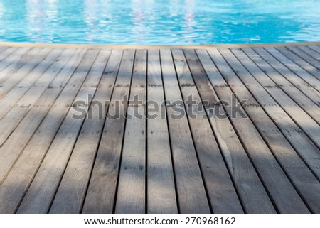 perspective view of wooden floor beside swimming pool