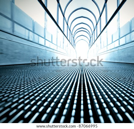 perspective view to modern steel blue escalator walkway inside spacious airport - stock photo