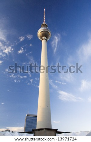 Perspective view up the Berlin Television Tower in the evening sunlight, with blue sky and a few fluffy white clouds - stock photo