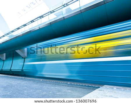 Perspective wide angle view of modern light blue illuminated and spacious public metro marble station with fast blurred trail of train in vanishing traffic motion - stock photo