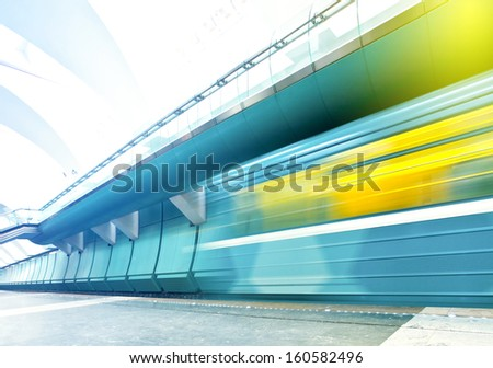 Perspective wide angle view of modern light blue illuminated and spacious public metro marble station with fast blurred trail of vivid yellow train in vanishing traffic motion - stock photo