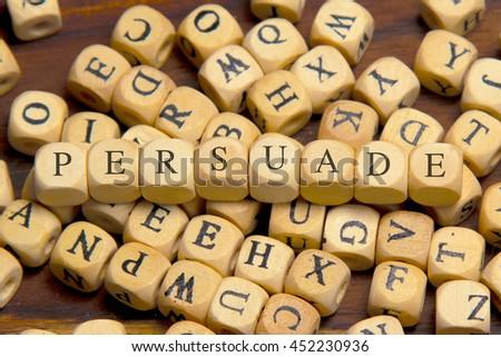 PERSUADE word written on wood block - stock photo