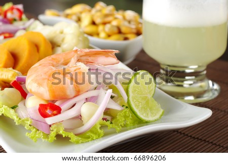 "Peruvian ceviche with king prawn accompanied by sweet potatoes, corn, cancha (fried corn) and the Peruvian cocktail called ""Pisco Sour"" (Selective Focus, Focus on the front of king prawn) - stock photo"