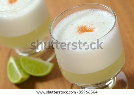 Peruvian cocktail named Pisco Sour made of Pisco (Peruvian grape schnaps),lime juice, syrup, egg white, and angostura (bitter fluid) drops on top (Selective Focus, Focus on the front of the angostura) - stock photo