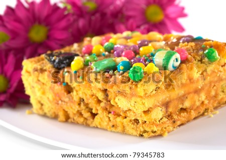 Peruvian colorful cake called Turron flavored with anis, sesame, dried fruits and honey and garnished with colorful sweets on top (Selective Focus, Focus on the front tip and the green ball on top) - stock photo