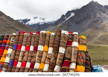 Peruvian colorful fabrics . Mountain background with snowy peaks - stock photo