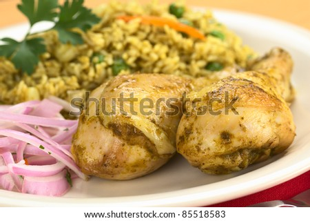 Peruvian dish called Arroz con Pollo (Rice with Chicken) made of rice, peas, corn, aji (hot pepper) and cilantro, served with Salsa Criolla (onion salad) (Selective Focus, Focus on the front) - stock photo