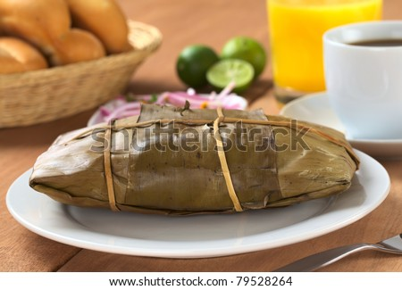 Peruvian food called Tamal which is prepared from cooked corn mixed with chicken and wrapped in banana leaves. It is eaten for breakfast or as appetizer at lunch (Selective Focus, Focus on the front) - stock photo