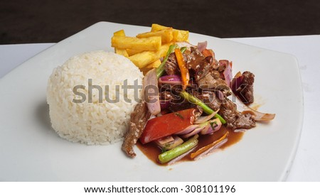 "Peruvian food ""lomo saltado"":A salted beef with tomatoes, onion, fried potatoes and rice. - stock photo"