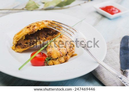 Peruvian snack called Empanada pie filled with ground beef meat and vegetables on a wooden table - stock photo