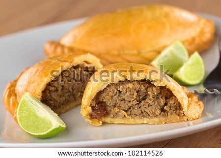 Peruvian snack called Empanada (pie) filled with ground beef meat, onion, raisin on plate with limes (Selective Focus, Focus on the empanada stuffing in the front) - stock photo