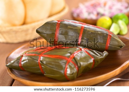 Peruvian tamales wrapped in banana leaves. Inside is a corn-based dough with meat, which are traditionally eaten for breakfast on Sundays (Selective Focus, Focus on the front of the upper tamale) - stock photo