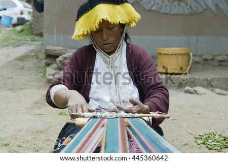 Peruvian woman weaving cloth on a hand loom. October 22, 2012 - Paru Paru, Andes Mountains, Peru - stock photo