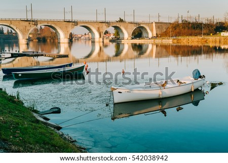 PESCHIERA DEL GARDA, ITALY - December 21, 2016: Boats anchored on the river Mincio. The Mincio is a river in northern Italy, the main outlet of the lake Garda and last left tributary of the Po river.