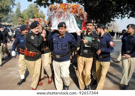 PESHAWAR, PAKISTAN - JAN 13: Police officials carry coffins of policemen, who were killed in militants attack at Sarband post, for burial after their funeral prayer on January 13, 2012 in Peshawar, Pakistan.