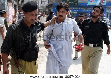PESHAWAR, PAKISTAN - JUL 06: Policemen escort a protester after his arrest during protest demonstration of Tehreek-e-Insaf (PTI) in favor of their demands at Yakatoot on July 06, 2011 in Peshawar. - stock photo