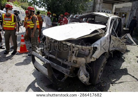PESHAWAR, PAKISTAN - JUN 11: Rescue officials busy in rescue work at the site after suicide bomb blast that targeted police vehicle on the convoy of (FRP) on June 11, 2015 in Peshawar.