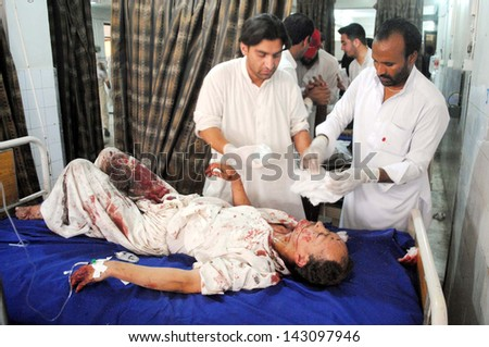 PESHAWAR, PAKISTAN - JUN 21: Victim of suicide bomb blast at Hussaini Madrassa  Chamkini area being admitted for treatment at Lady Reading hospital, on June 21, 2013 in Peshawar.