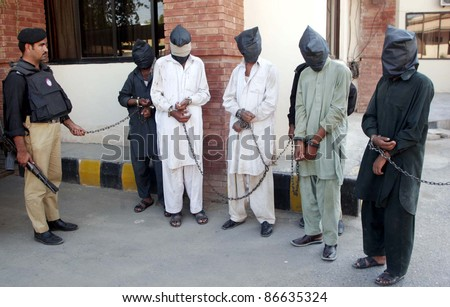 PESHAWAR, PAKISTAN - OCT 14: Policemen escort handcuffed assailants (face covered with cloths), who attacked policemen and killed two Khazana policemen at the police station in Peshawar, Pakistan on Oct. 14, 2011.
