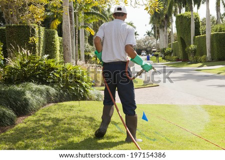 Pest control technician using high pressure spray on lawn - stock photo