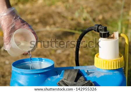 Pesticide being added into  a sprayer using a measuring cup - stock photo