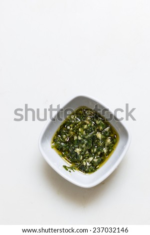Pesto sauce  in a dipping bowl on simple white background - stock photo
