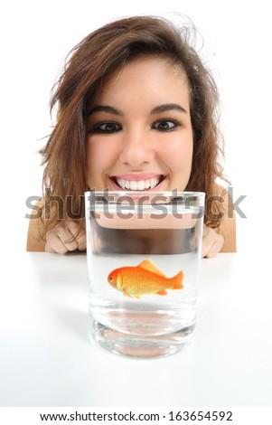 Pet fish in a glass needs care and a woman looking it isolated on a white background            - stock photo