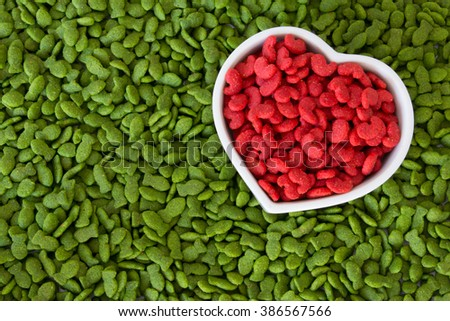 pet food in heart cup with green color on background - stock photo