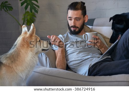 Pet owner talking to his pet dog on the couch sofa, loving affectionate bond